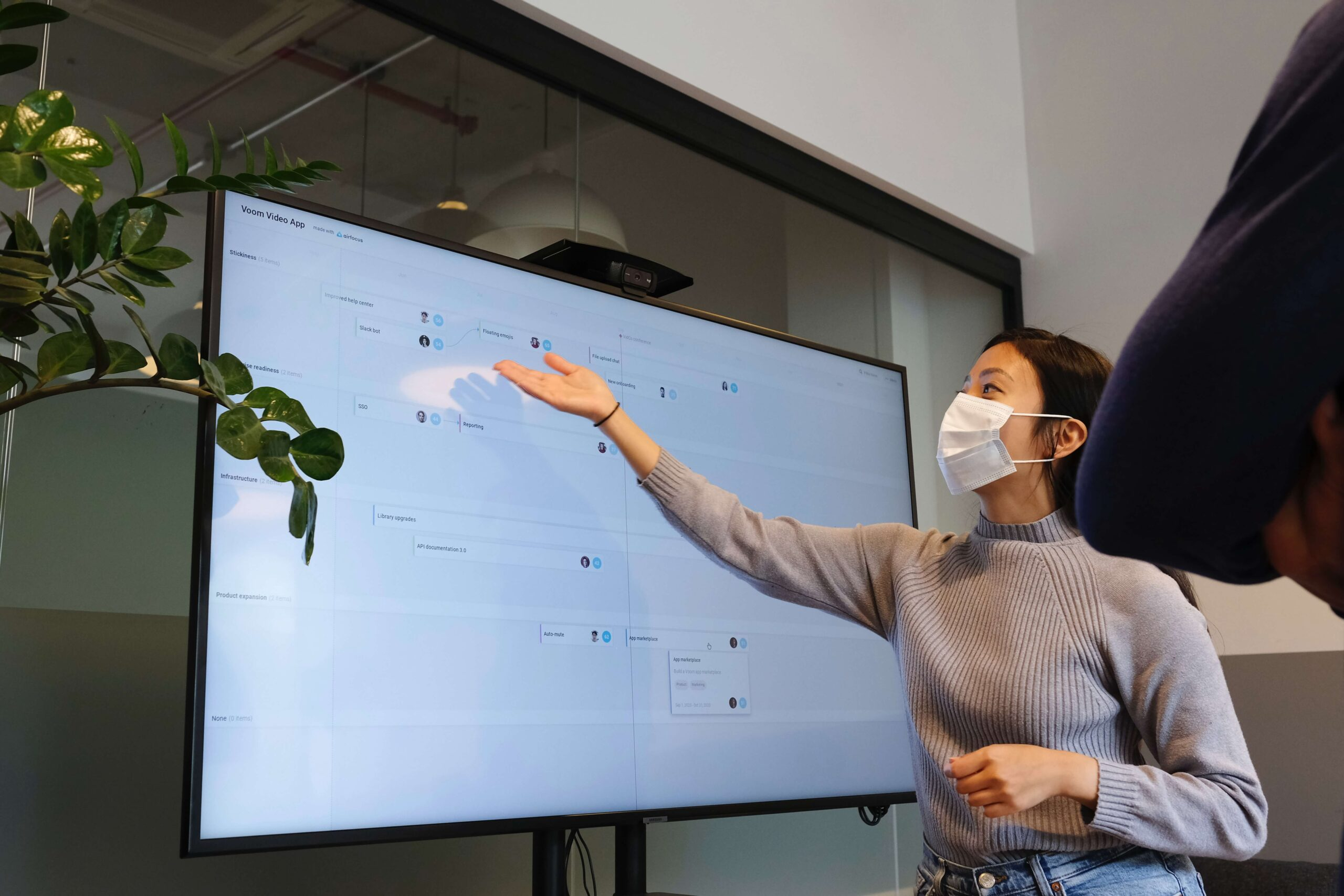 woman wearing a mask giving a presentation in a conference room using a digital display